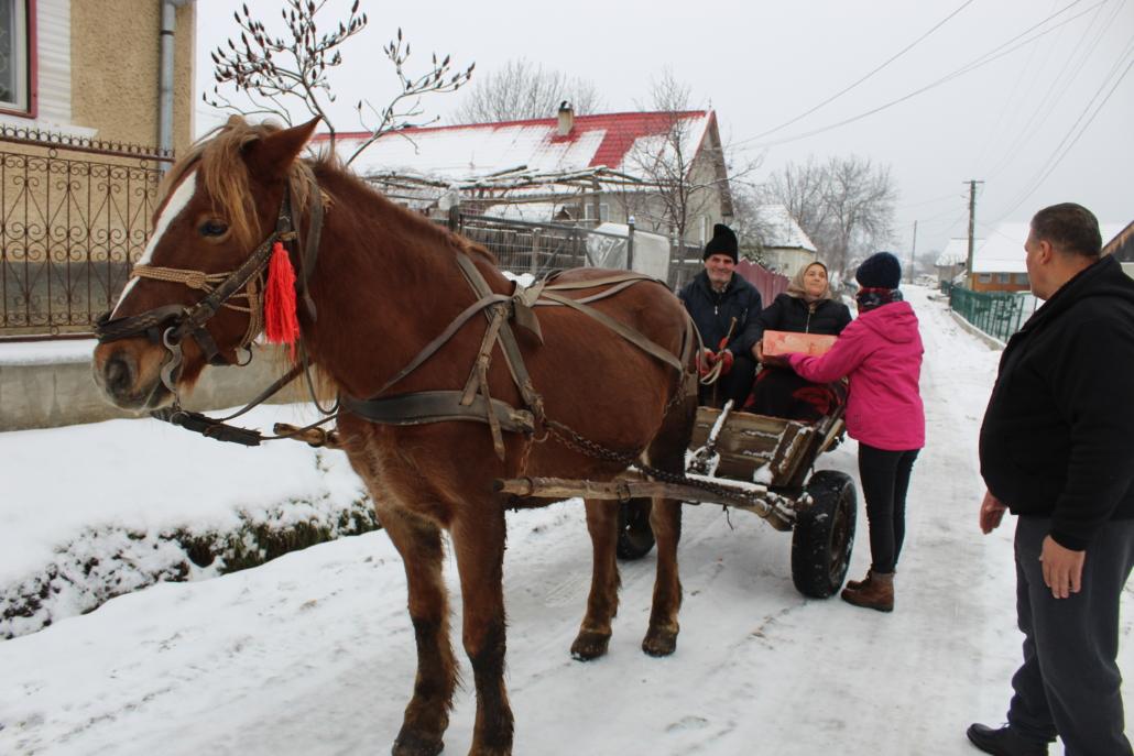 Mitarbeiter des CHD übergeben ein Weihnachtspaket Personen auf einer Pferdekutsche