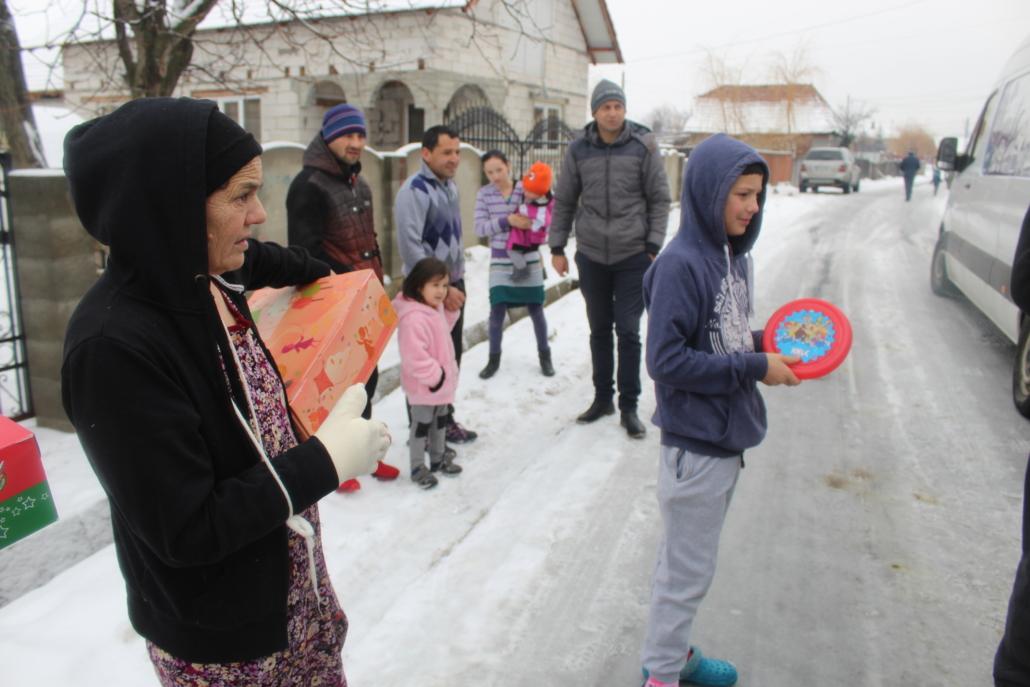 Mehrere Personen auf einer Straße mit Weihnachtspaketen